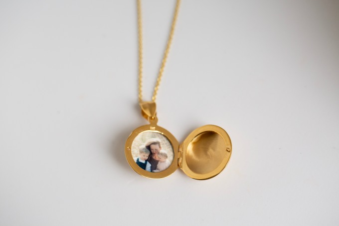 round gold locket with photo inside